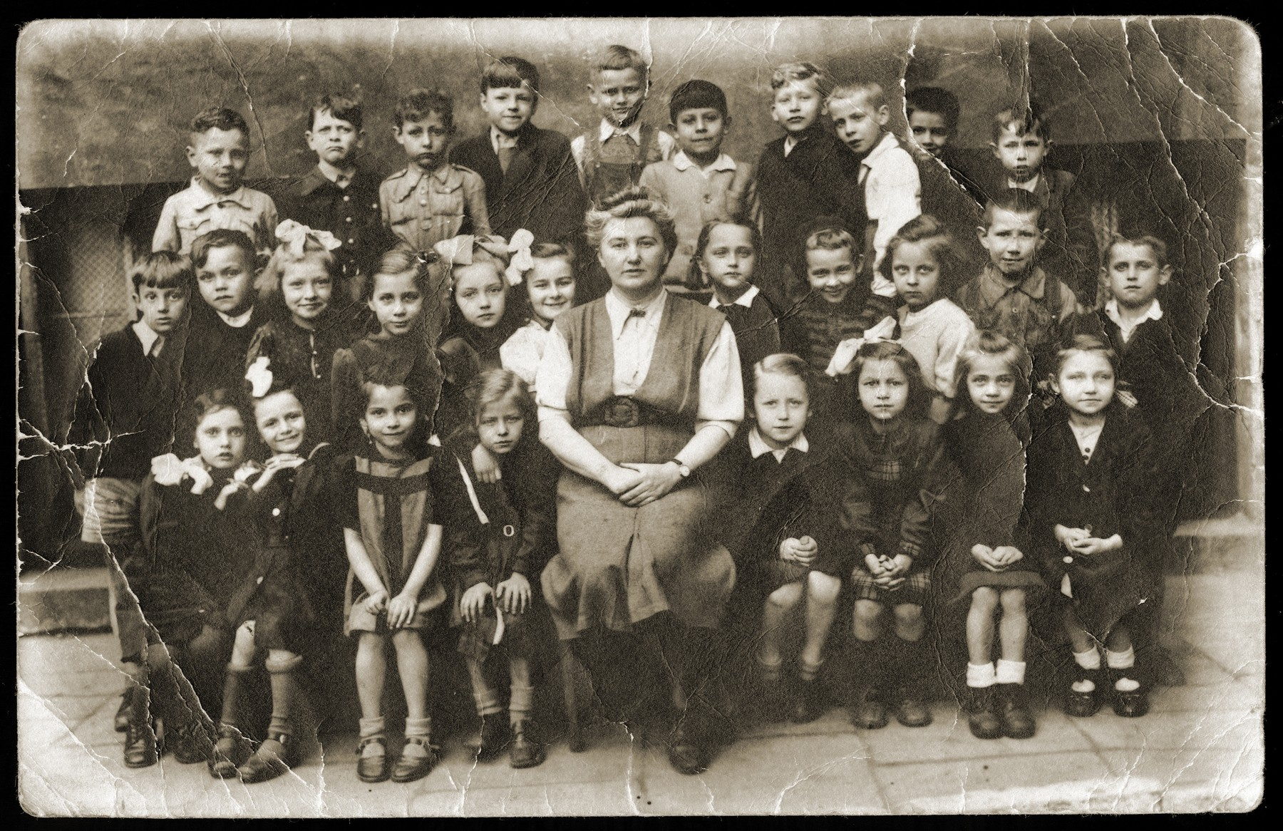 Group portrait of the pupils and teacher of a first grade class in Lodz.    Among those pictured is Anna Strzelczyk (front row, left).  The two girls beside her are also Jewish children who were hidden during the war.