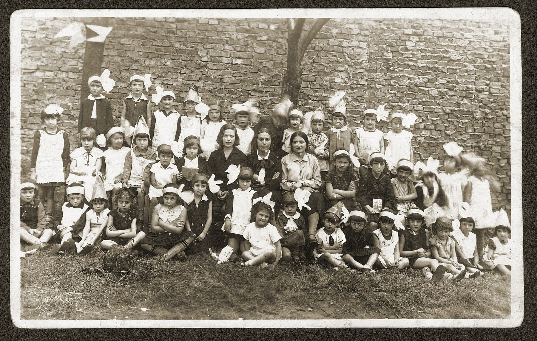 Group portrait of Jewish children and their teachers in a Bedzin kindergarten.    Among those pictured is Fela Fiszel (front row, second from the right).