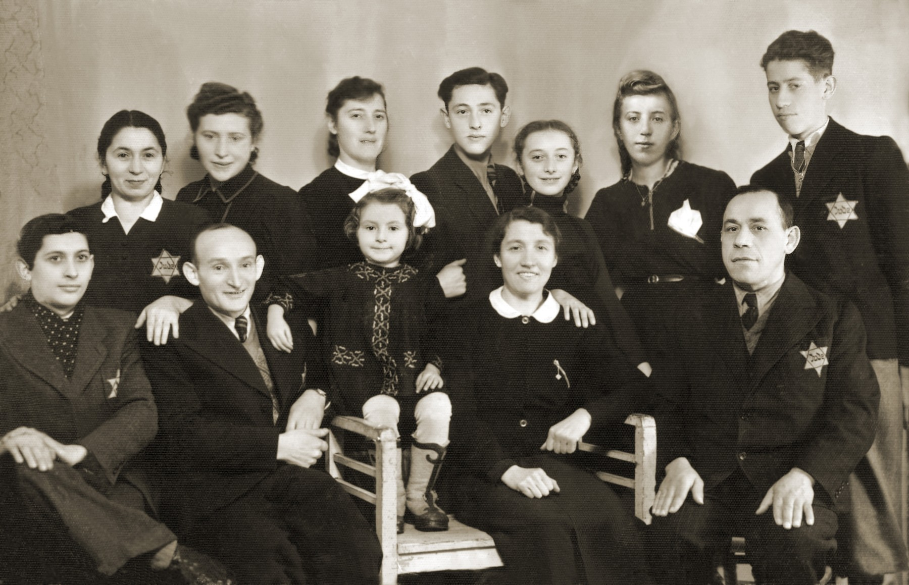 Group portrait of members of the extended Gipsman family in the Bedzin ghetto.  Pictured in the back row, from left to right are: Lea and Chawa Gipsman; Chaja Gitla Gipsman; Natan Gipsman; Maniusia Gipsman; Regina Fajerman; and Maks Zylbersztajn.  Seated in the front row, from left to right are: Herman Zylbersztajn; Wolf Gipsman; Dina Gipsman; Sara Zylbersztajn; and Moryc Zylbersztajn.