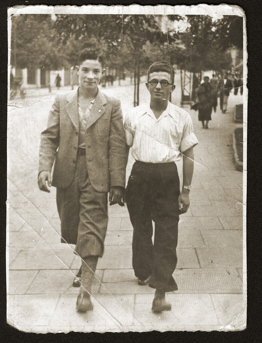 Two Jewish teenage boys walk along a street in Bedzin, Poland.  Pictured are Jakob Fiszel and a friend. Jakob was a student at the Stadler school in Bedzin.