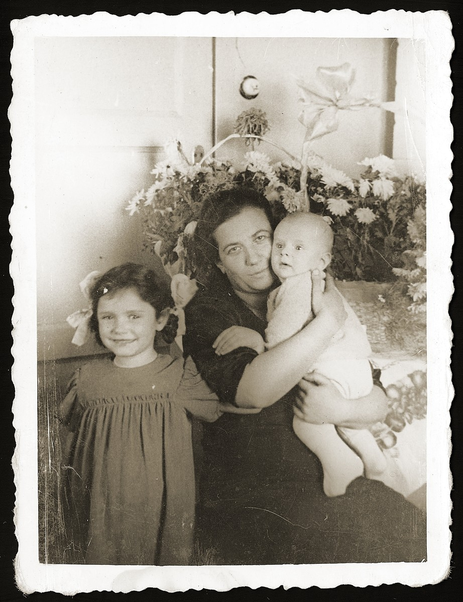 Jewish rescuer Madzia (Jozefowicz) Strzelczyk poses with her newborn son, Marian, and adopted daughter, Anna, soon after the liberation.