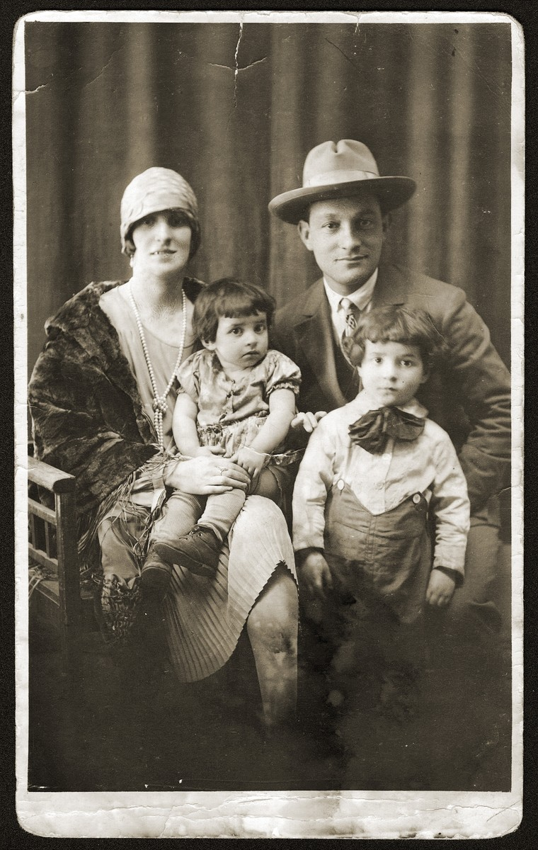 Studio portrait of a Jewish family in Bedzin, Poland.  Pictured are Sara Bajla and Mosze Fiszel with their two children, Fela (front left) and Jakob (front right).