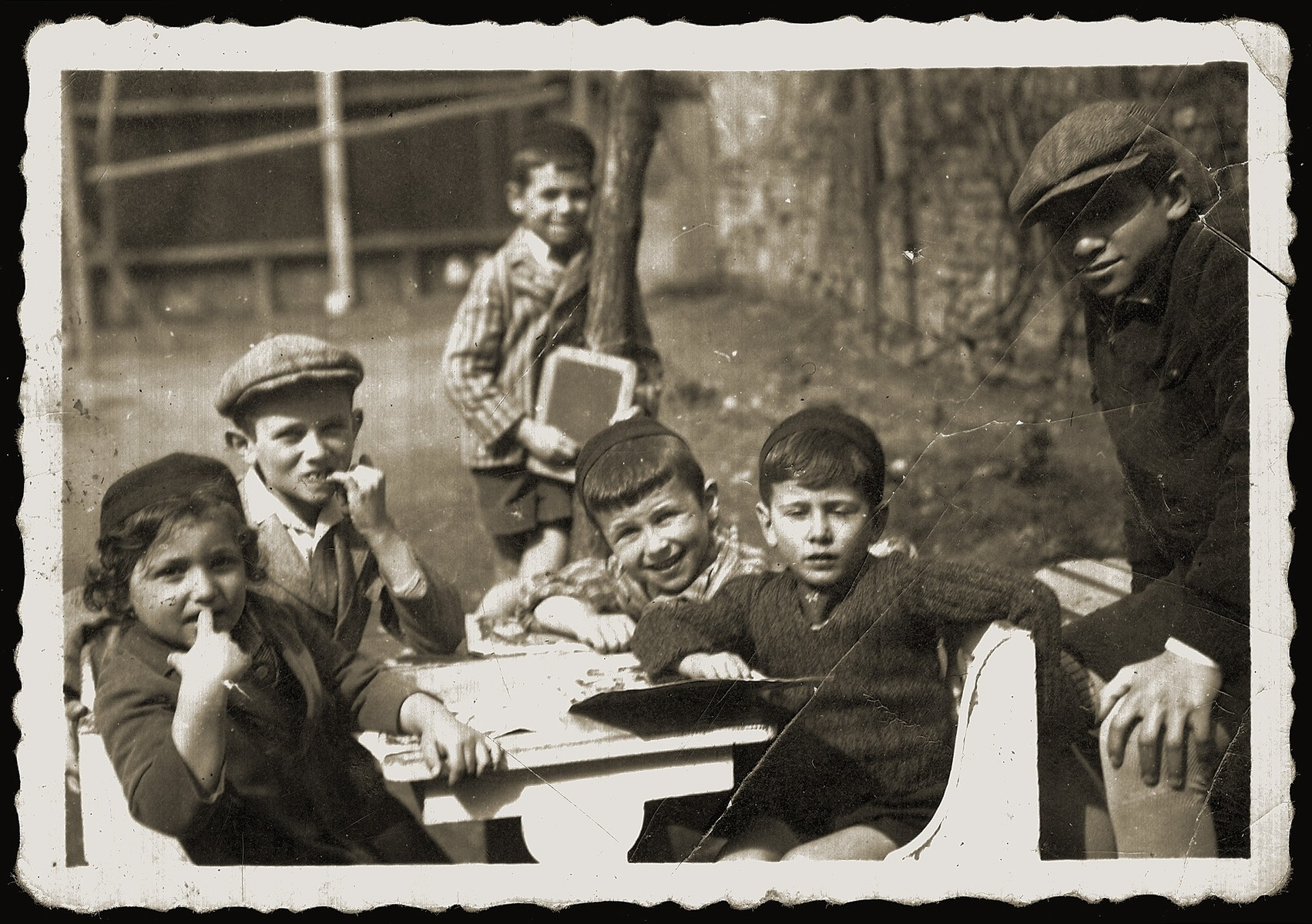 A group of Jewish children seated outside around a table.  Pictured are the donor's brother, Akiva Schwarcz (behind), and her four nephews.