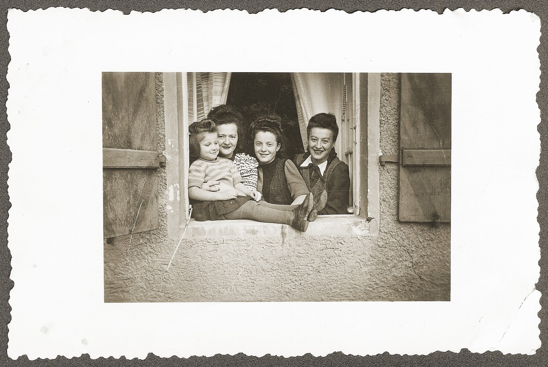 A group of Jewish DPs pose in the window of their residence in Woerth an der Donau.  Pictured from left to right are: Mania Sztajnman, Toby Frimmerman Sztajnman (holding Mania), Nacha Kleinberg, and Chava Frimmerman.