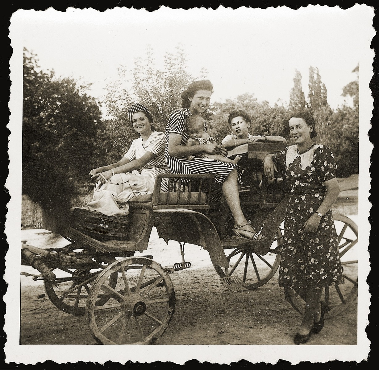 Miriam Schwarcz (holding her nephew), poses in an open carriage with her sister Lilly (left) and other relatives.
