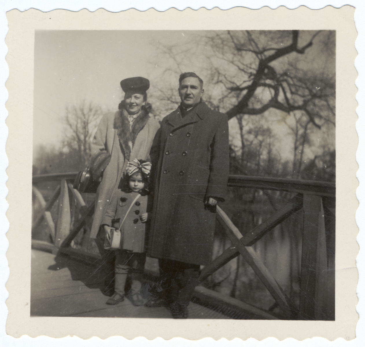 A Polish Jewish couple poses on a bridge with their adopted daughter and biological niece.  Pictured are Sara, Krystyna (Lindenbaum) and Bernard Kuniegis.
