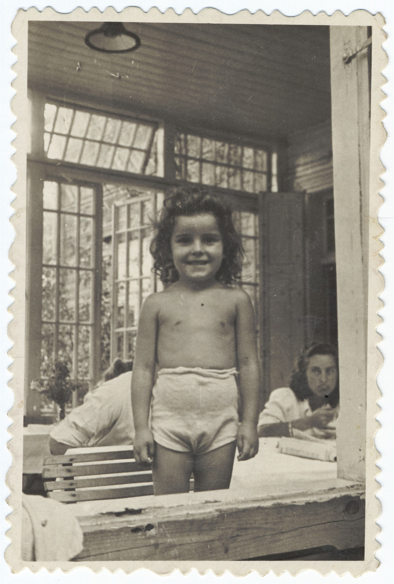 A young Jewish girl poses in her underwear in a summer colony outside of Warsaw where she has gone to recuperate after the war.