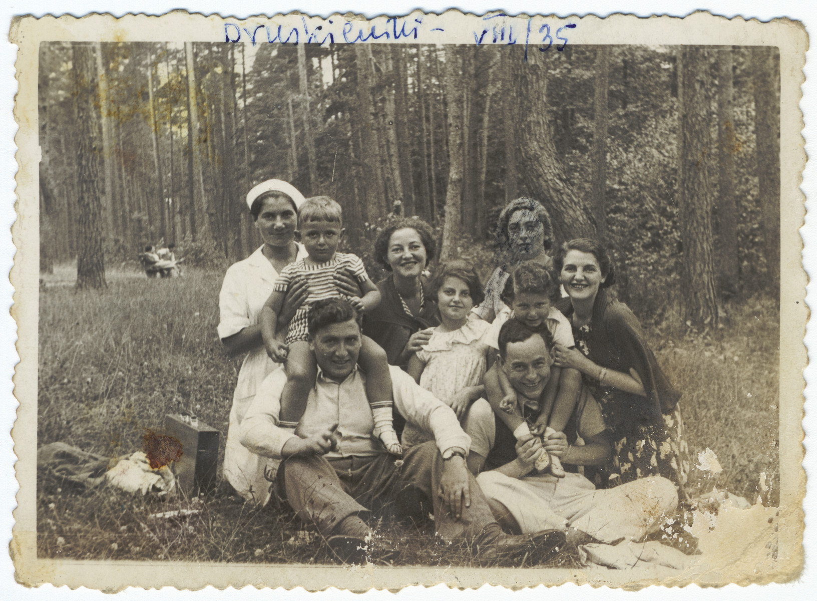 A group of friends and relatives vacations in a summer resort in the woods.  Among those pictured are Bernard Kuniegis with his son Jerzy on his shoulders on the right.  His wife Sara whose face is partially blotted out is behind him.