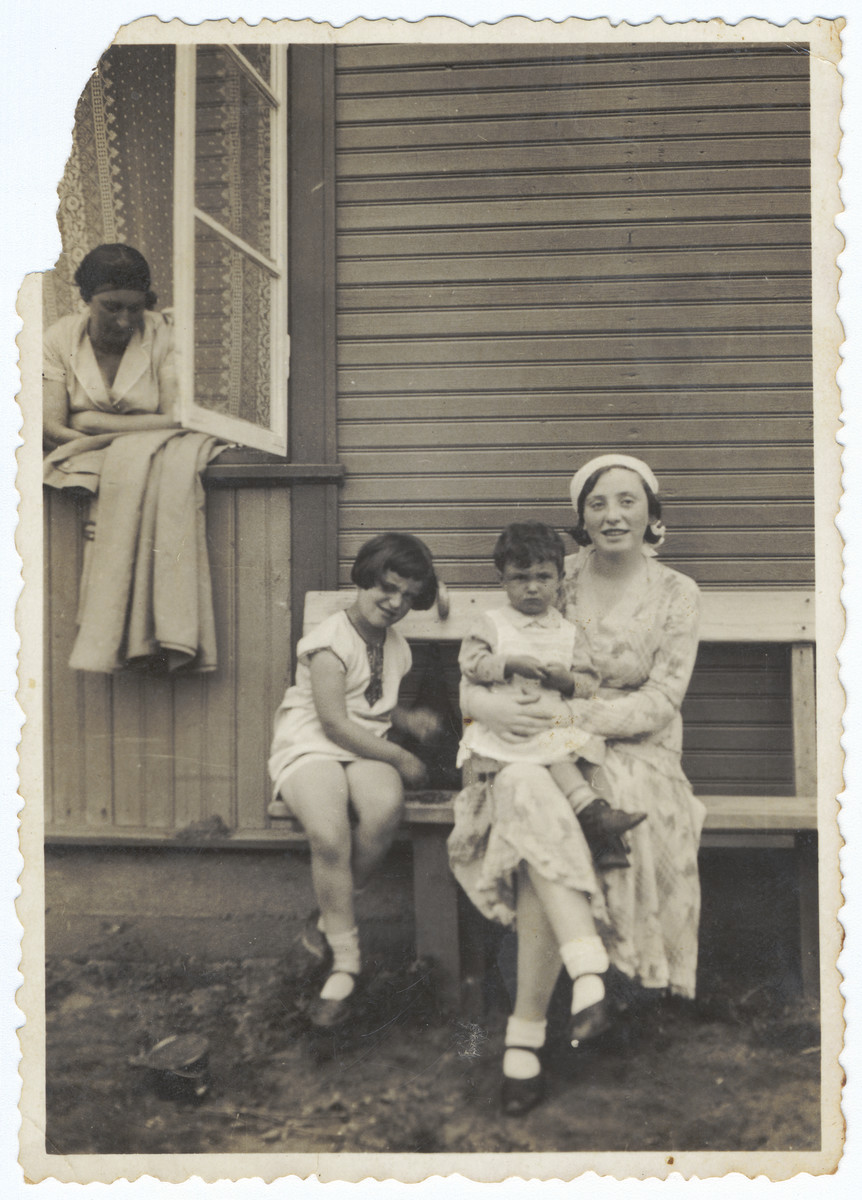 A Lithuanian-Jewish family poses on a wooden bench outside a summer home on the outskirts of Kaunas.  Rina Ilgovsky is sitting on her cousin's lap.  Her mother Hadassah Ilgovsky is looking out the window.