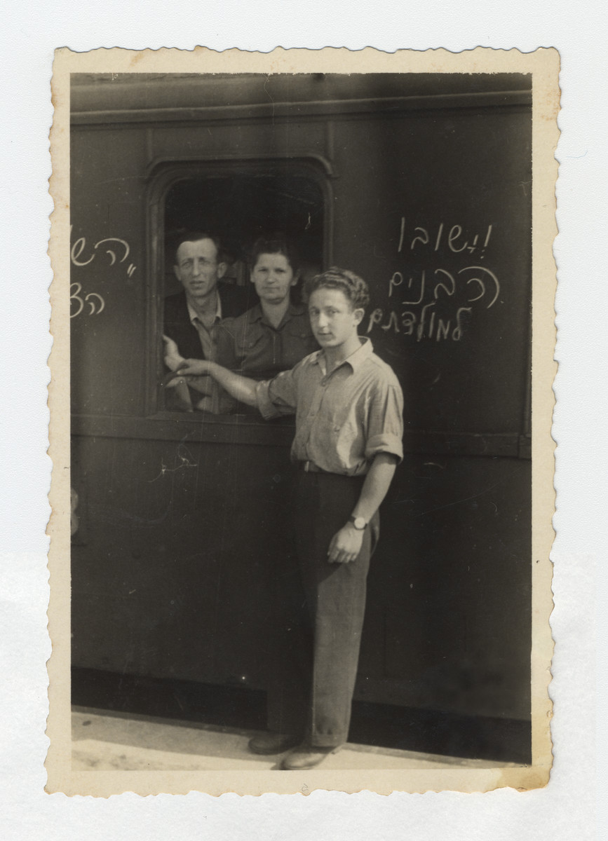 """Max Schanzer says farewell to his parents through a train window prior to their departure to Palestine.  The writing on the train reads """"the sons shall return to their homeland""""."""