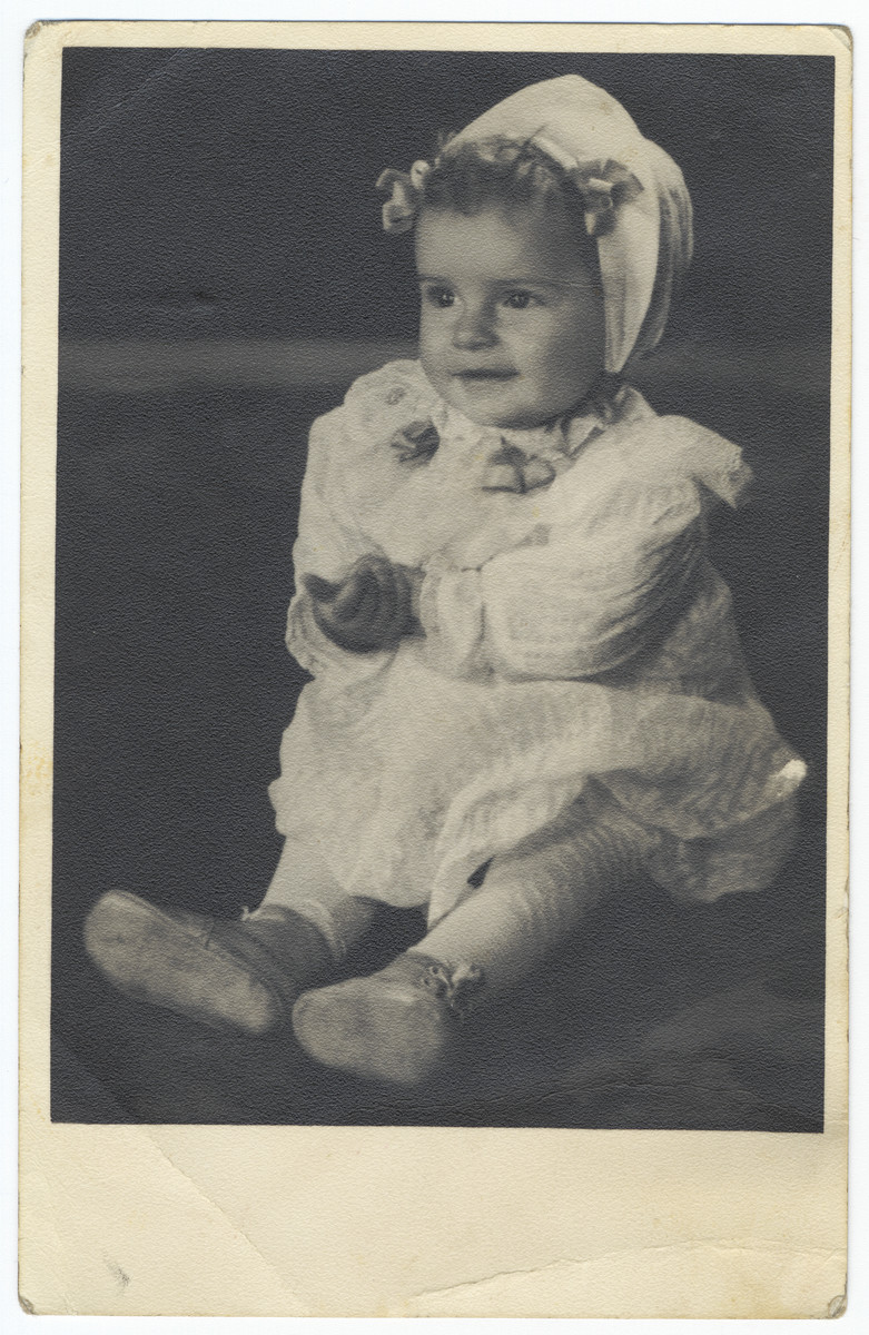 Studio portrait of a young Jewish girl in hiding in her baptismal gown.