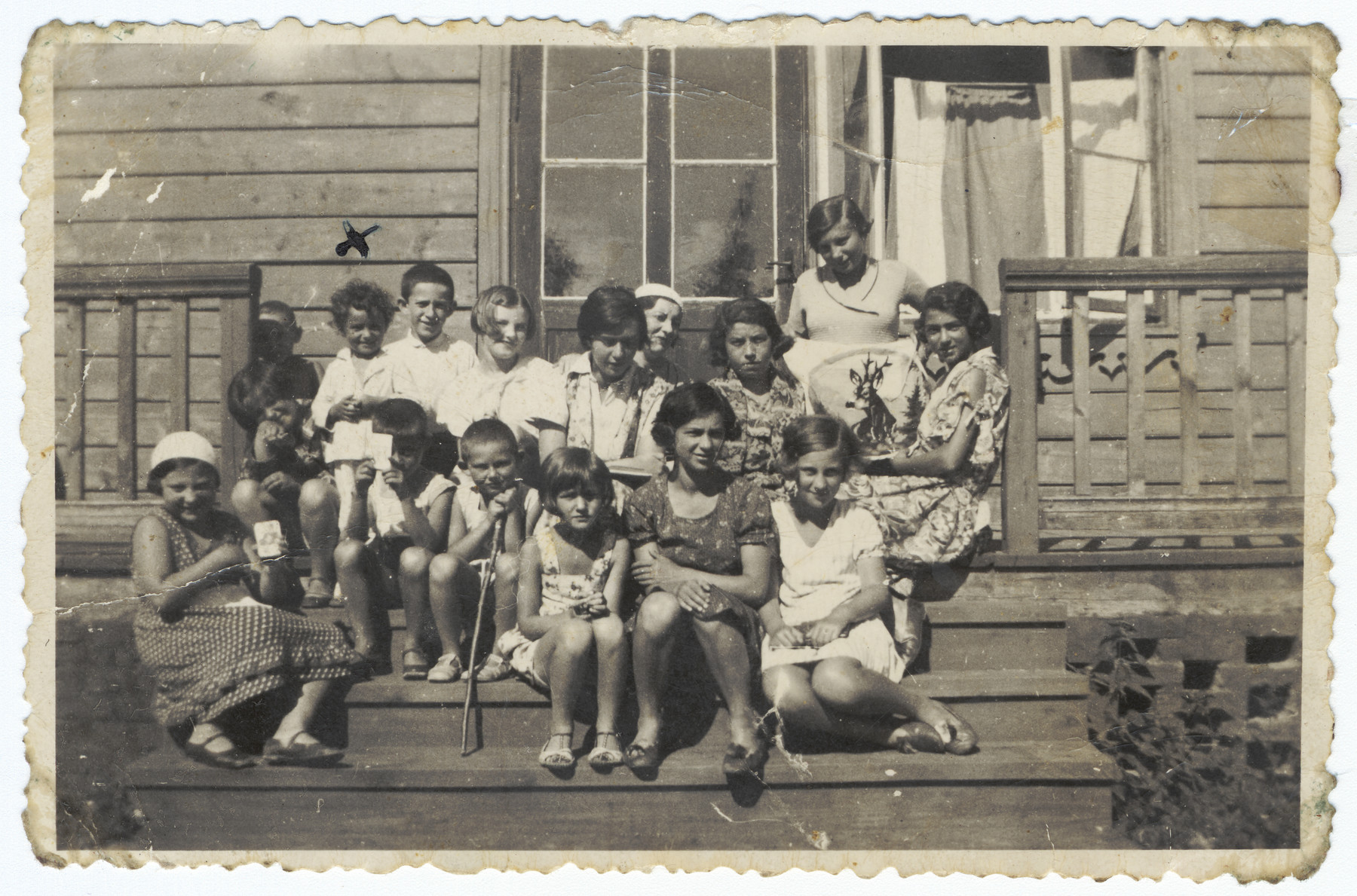A large group of Lithuanian Jews pose on the steps of a wooden building in a summer colony in Palanga.  Pictured at the top left under the x is Rina Ilgovsky.