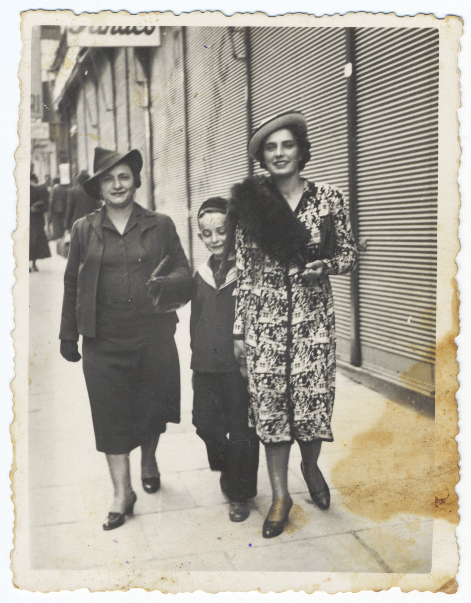 A Romanian Jewish family walks down a street in Cernauti.  Pictured are Slima Engler, her son Shneur and sister Malka Zlocsower.