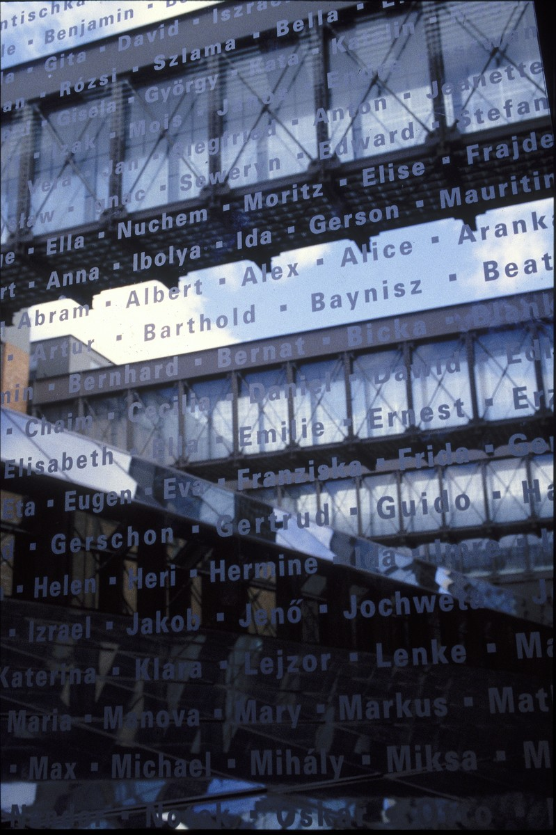 Detail of an interior bridge at the United States Holocaust Memorial Museum with the names of victims etched in glass.