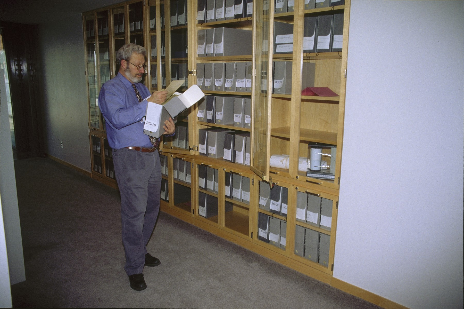Chief Archivist Henry Mayer examines a document while standing in front of a row of glass cases on the fifth floor of the U.S. Holocaust Memorial Museum.