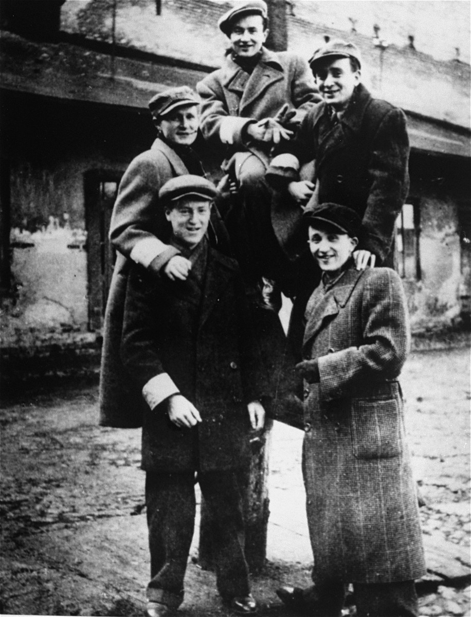 Five Jewish teenage boys pose outside in a pyramid in the Piotrkow Trybunalski ghetto.    Pictured clockwise from the top are: Nuno Basior, Shaya Samelson, ? Basior, Velvel Samelson, and unknown.