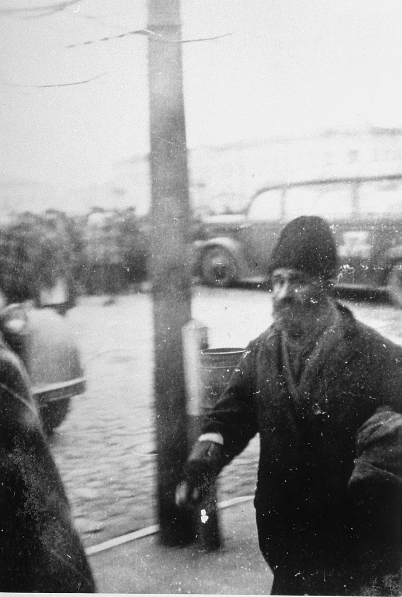 A Jewish man walks along the sidewalk near the town square in Raciaz.