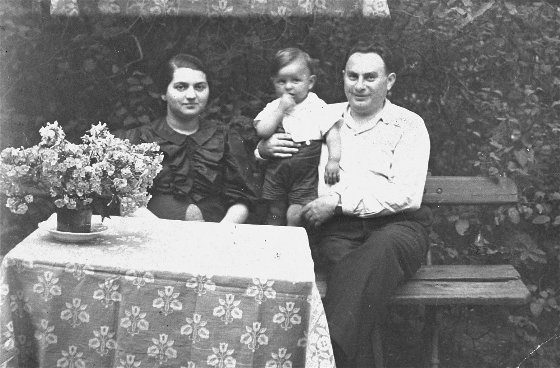 A Jewish couple sits outside with their son in Plonsk, Poland.  Pictured are Irena and Zygmunt Fuks with their son Mietek.    The donor is the niece of Zygmunt and Irena Fuks.  Zygmunt perished in a concentration camp in 1943; Mietek was reportedly buried alive in 1943; the fate of Irena is unknown.