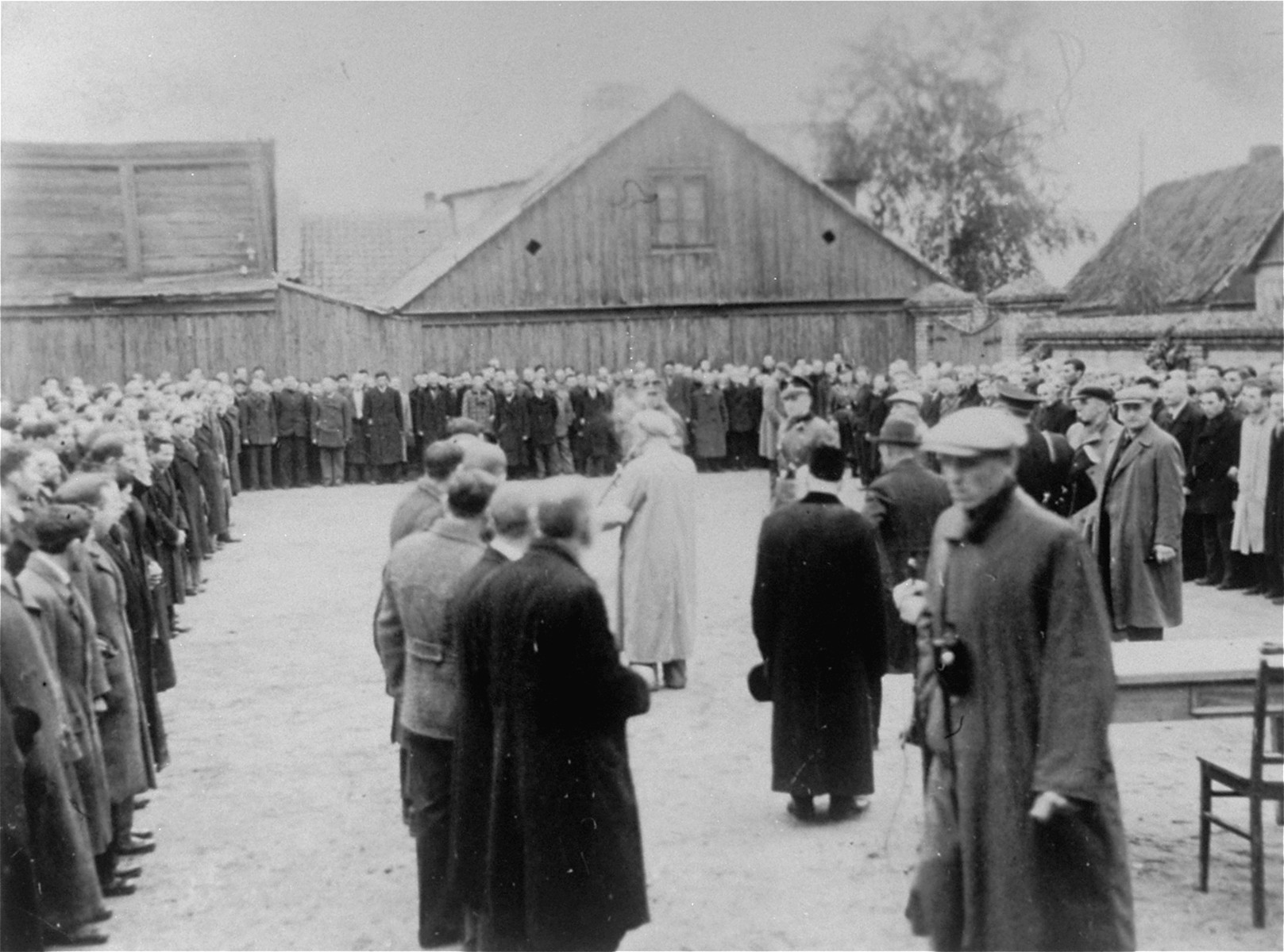 Jewish men are assembled in a large courtyard or public square in Raciaz.