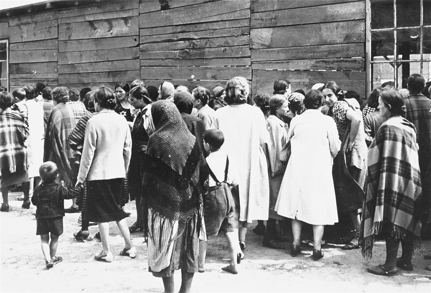 Jewish women and children are gathered outside a wooden barracks in Piotrkow Kujawski.