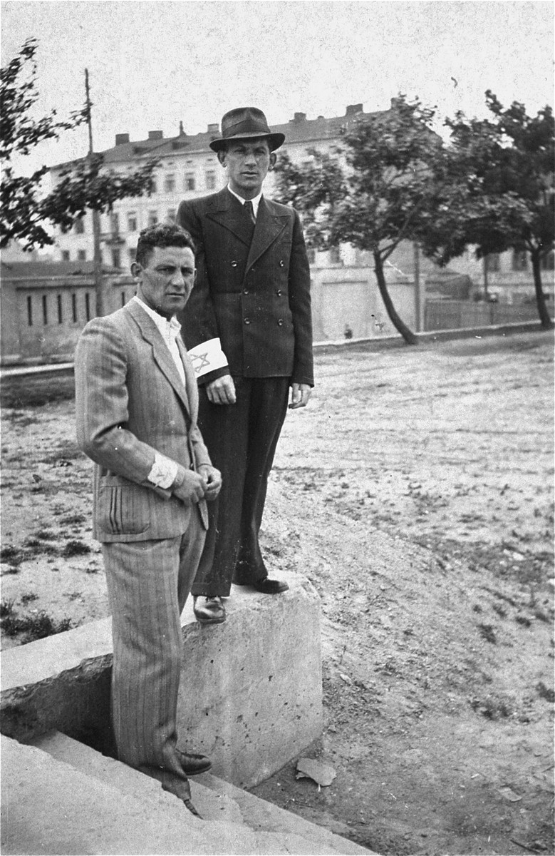 Two young Jewish men stand outside near the military barracks in Piotrkow Trybunalski.  Pictured are Binem Jachimowicz and Moshe Blumstein.  Four days after this photograph was taken the Jews of Piotrkow were assembled for deportation at this site.