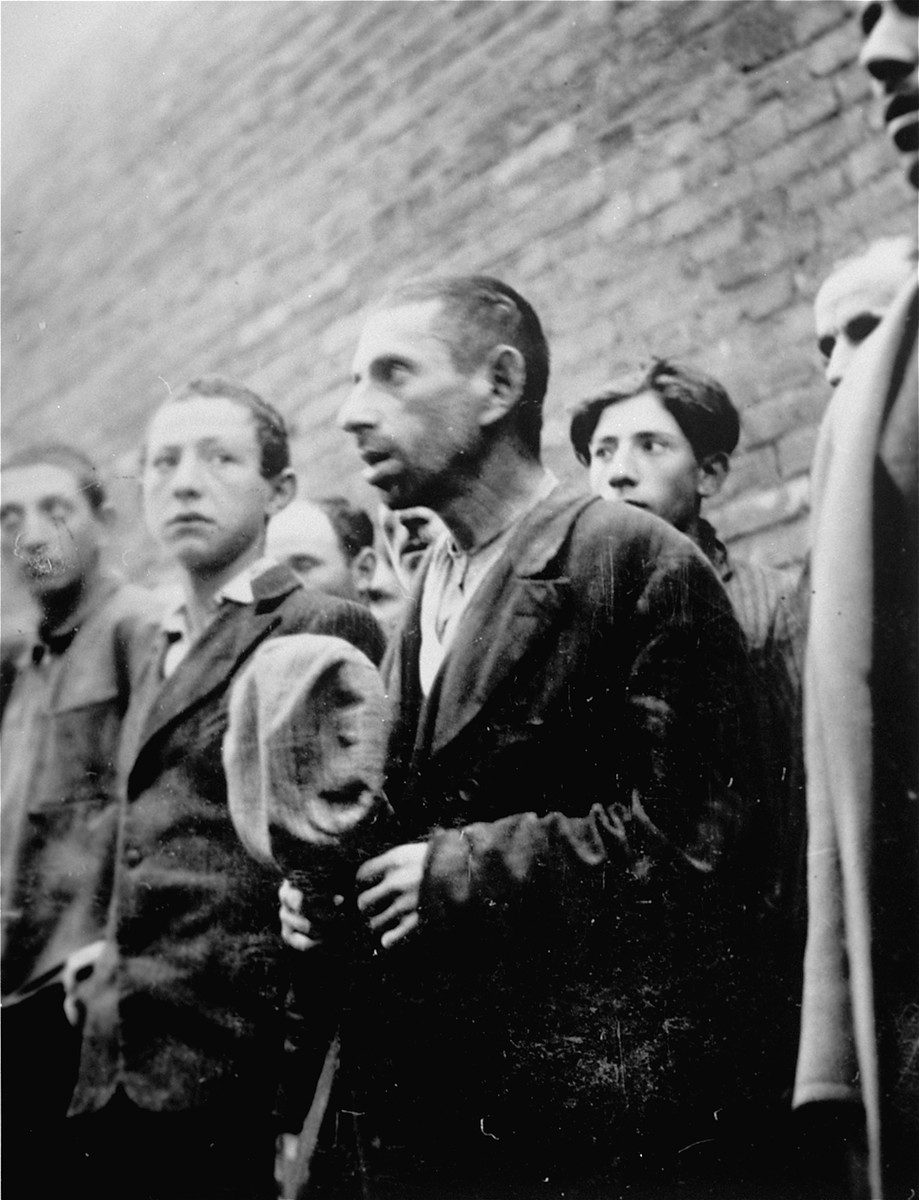 Jewish men and youth are lined-up against a wall during an action in Plonsk.