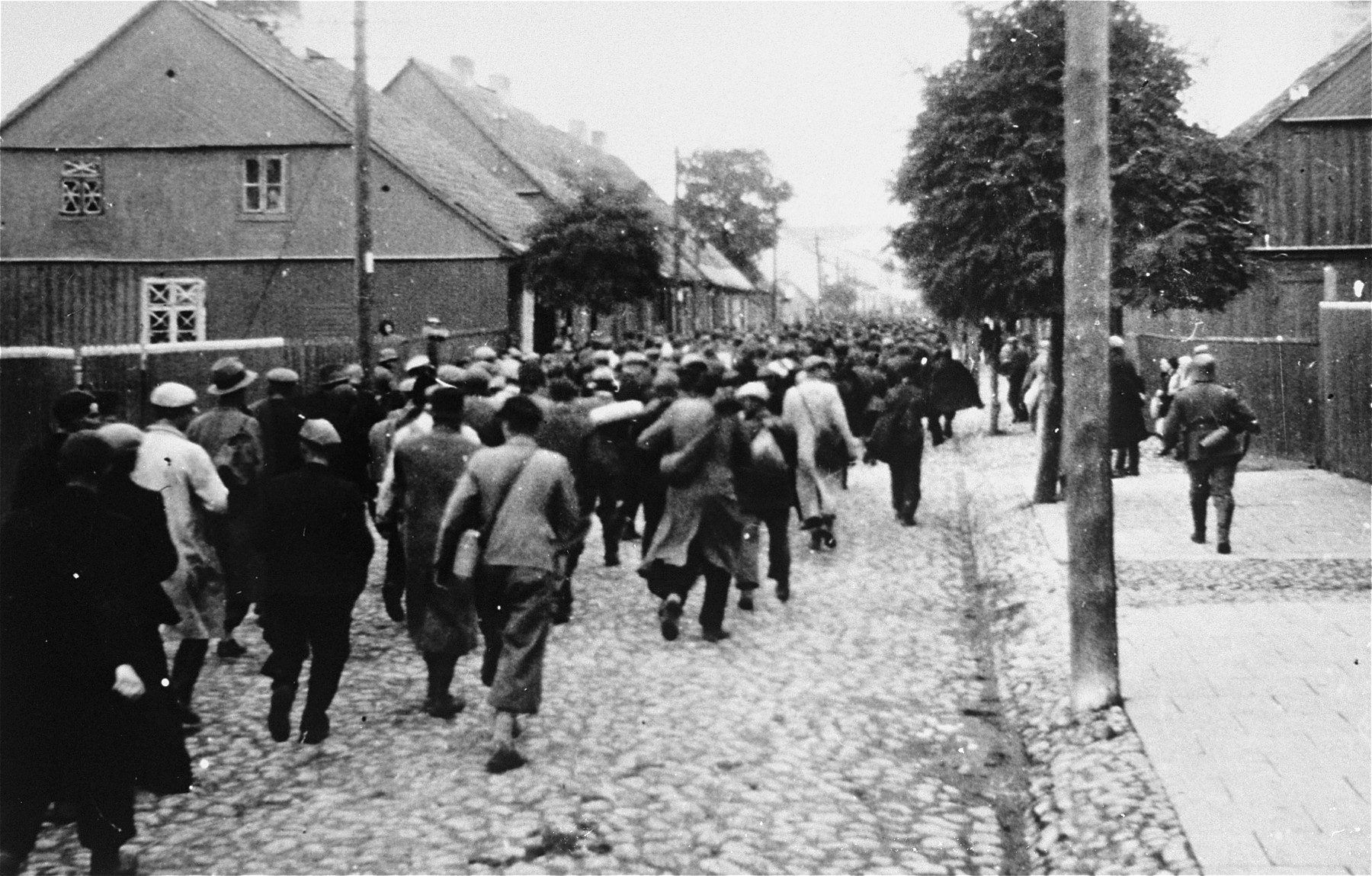 Jewish men are marched through town during a deportation action in Plonsk.