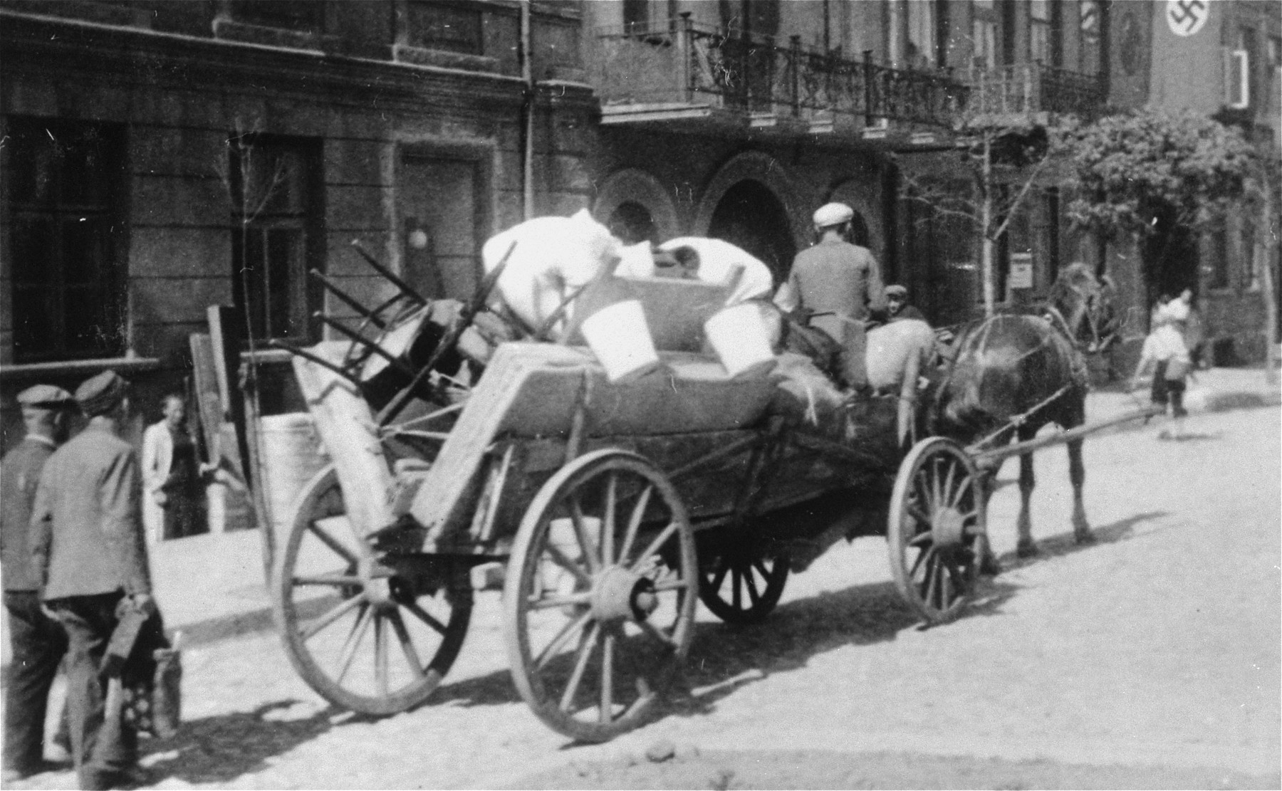 "A Jew drives a horse-drawn wagon bearing furniture and household goods along a street in Plonsk.  The original German caption reads: ""Juden raus!"""