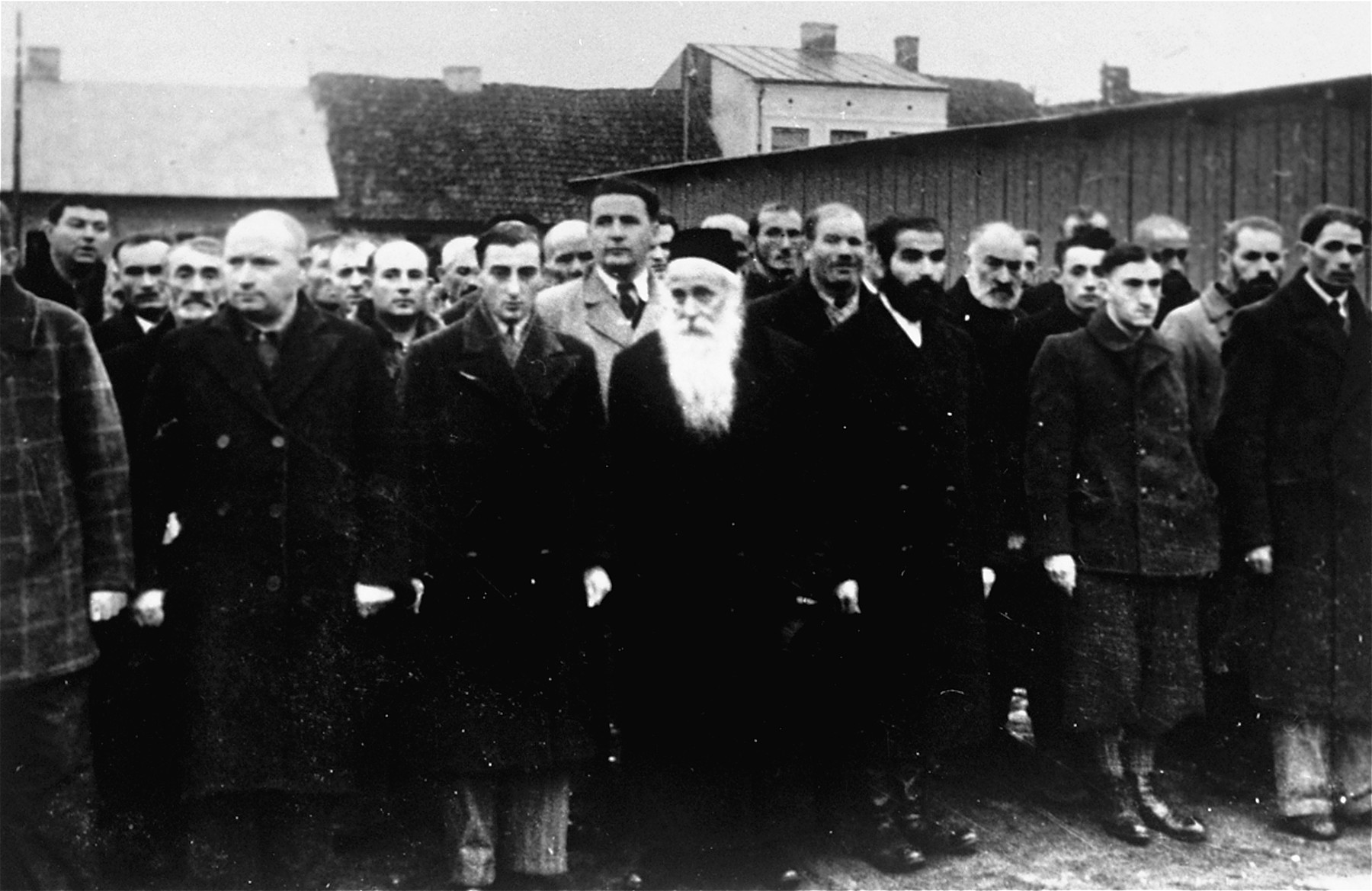 Jewish men are lined up in a courtyard or public square in Raciaz.  Among them is an elderly rabbi.