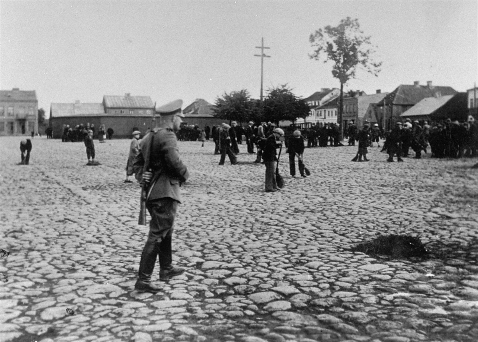 An SS member oversees a group of Jewish men at forced labor sweeping the pavement of the town square in Raciaz.