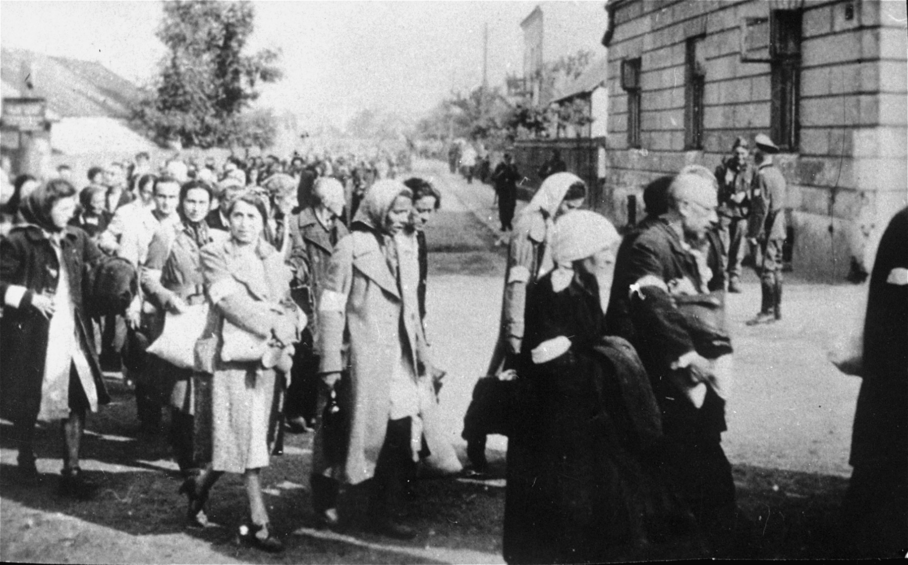 Jews walk in a long column through the streets of Rzeszow during a deportation action from the ghetto.