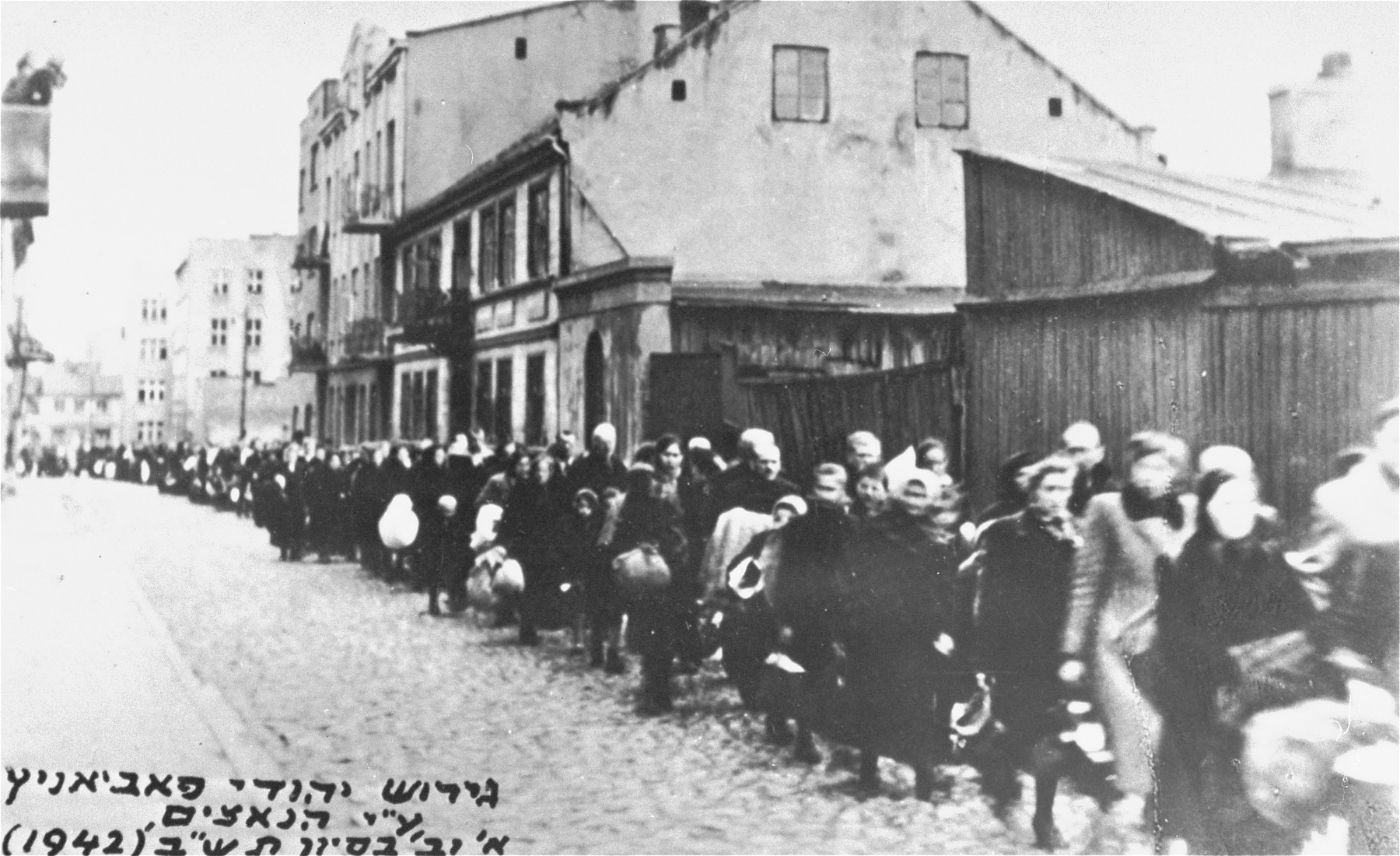 A long column of Jews marches through the streets of Pabianice during a deportation action.
