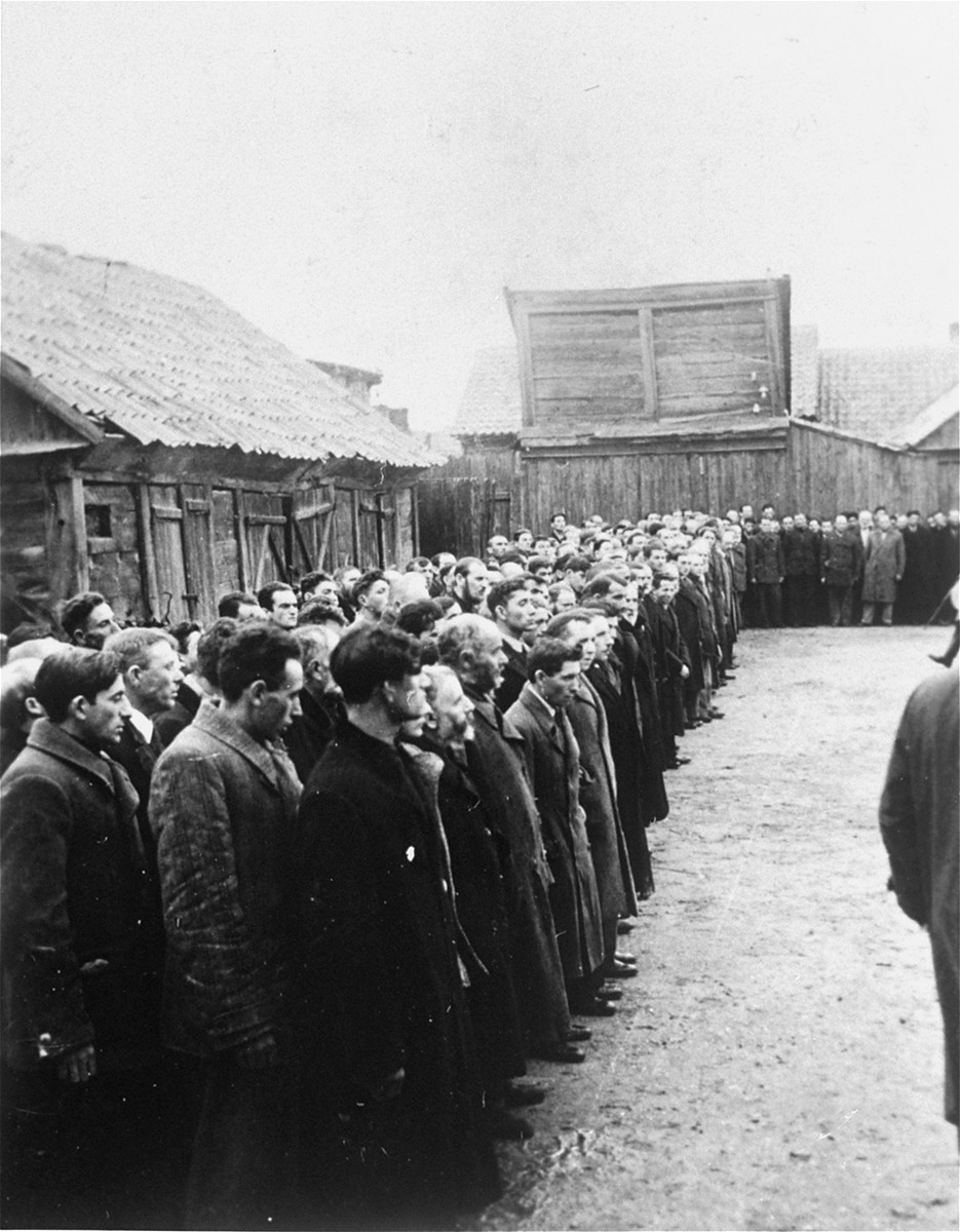 Jewish men are lined up in a large courtyard or public square in Raciaz.