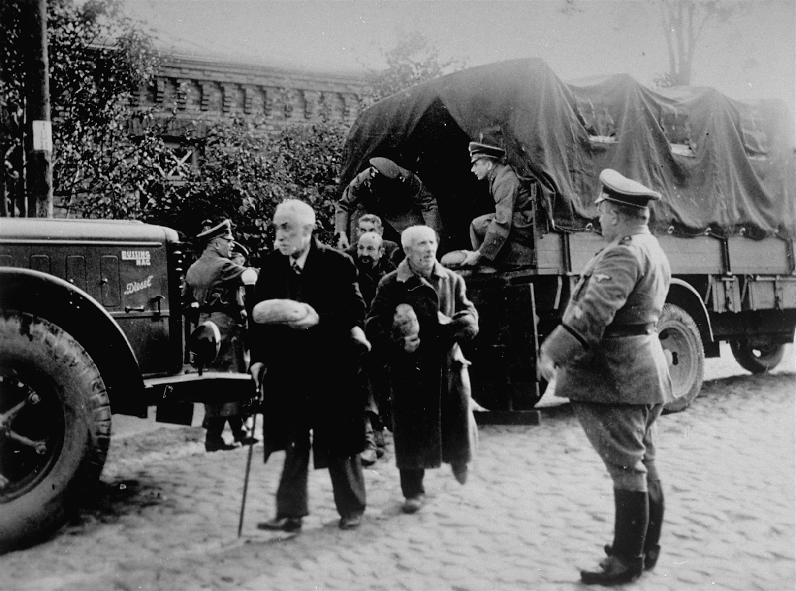 Jewish men from Plonsk receive loaves of bread that Germans distribute from the back of a truck.