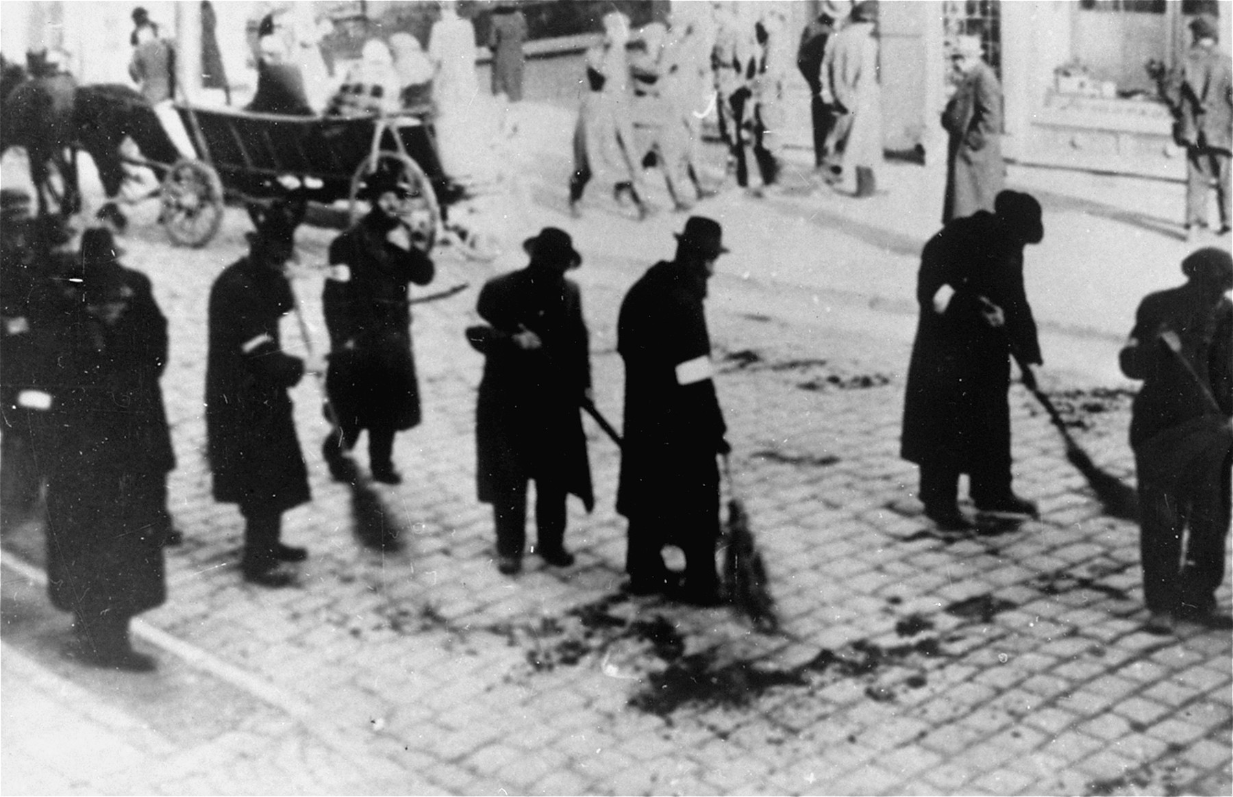 Jews are forced to sweep the street in the Rzeszow ghetto.