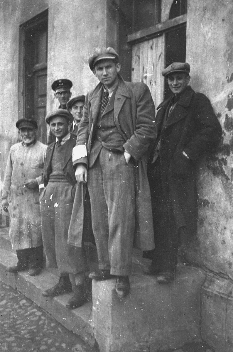 A group of Jewish men stand at the entrance to the mikve (ritual bath) in the Piotrkow Trybunalski ghetto.   Among those pictured are: Leib Schwartz, Israel Weiss, Binem Jachimowicz, Moshe Chmielinitzky and Eliahu Bendermacher (the Jewish policeman in the background).