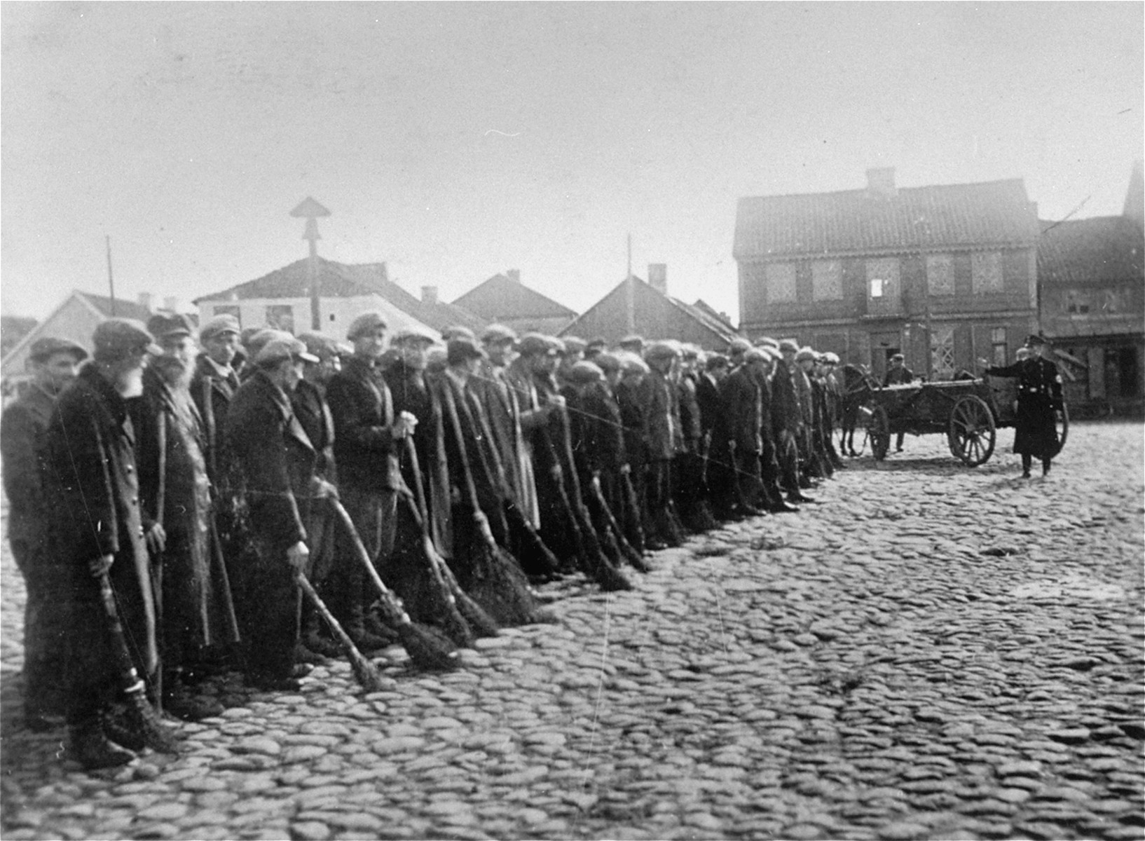 Jewish men are lined-up with brooms in the town square of Raciaz.