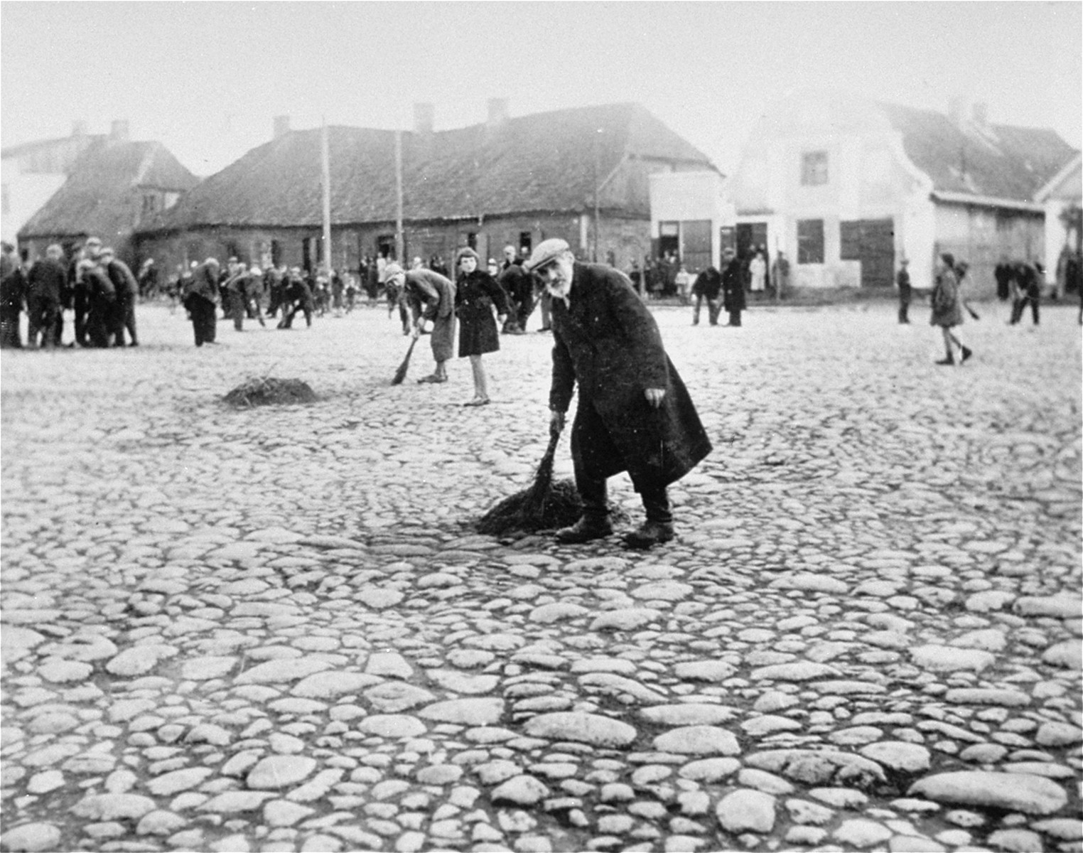 Jews are forced to sweep the pavement in the town square of Raciaz.