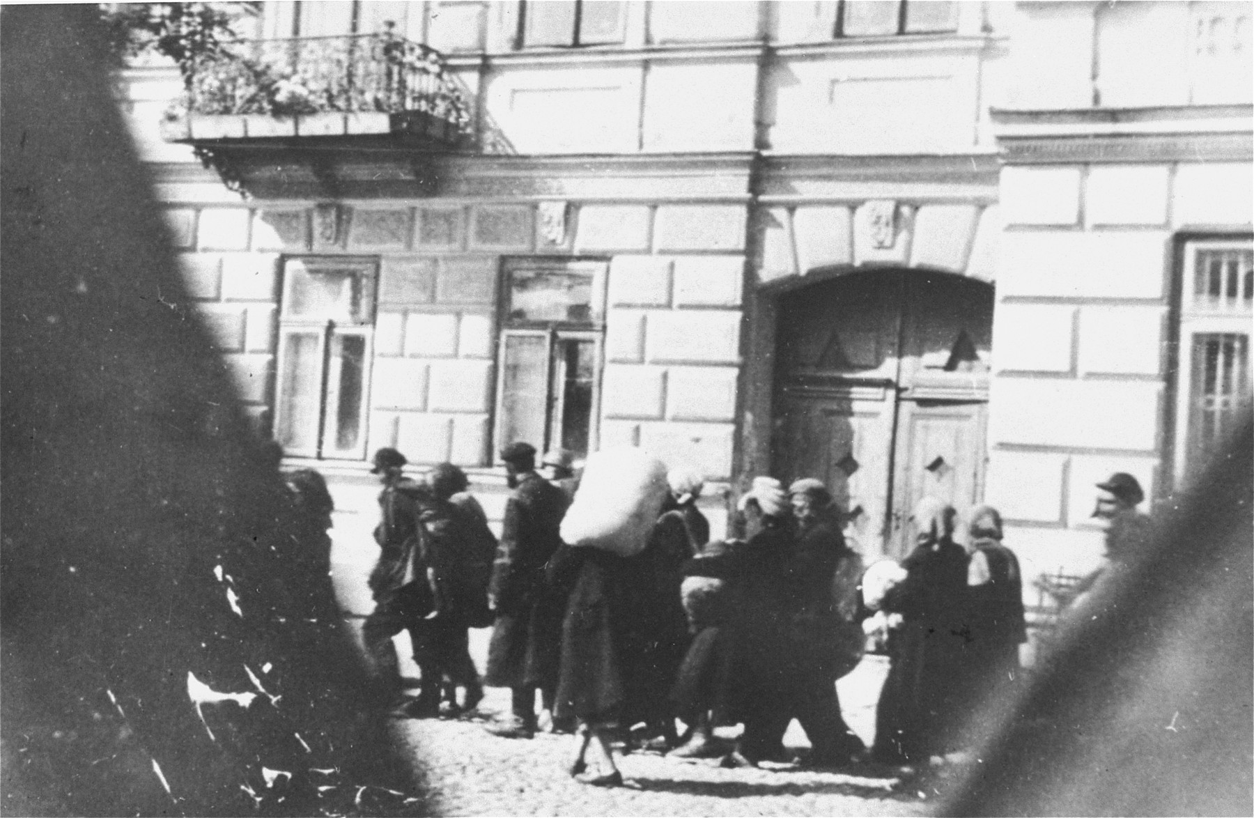 Jews are led through the streets of the town on their way to the railroad station during a deportation action from the Siedlce ghetto.  One of a series of clandestine photographs taken by a member of the AK (Polish Home Army) underground.