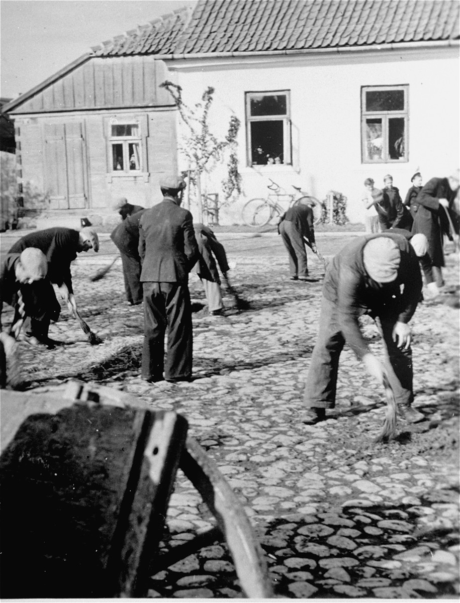 Jewish men are forced to sweep the pavement in the town square of Raciaz with short brooms.