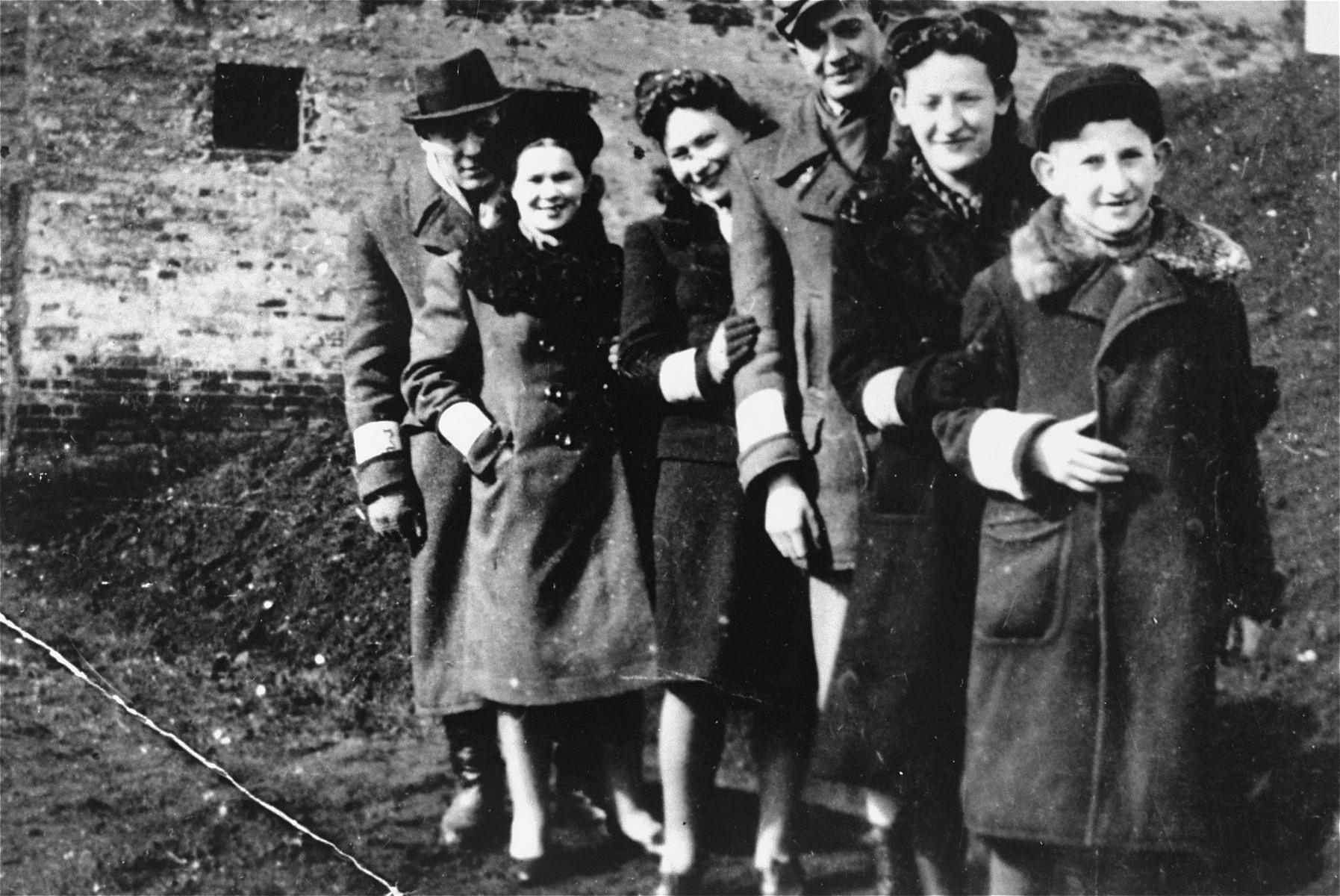 Group portrait of six young Jewish men and women in the Piotrkow Trybunalski ghetto.  Pictured from left to right are: Abram Zarnowiecki, Rozia Zarnowiecki, Mania Freiberger, Moniek, Rachel Zarnowiecki, and Chaim Zarnowiecki.  All perished during the war.