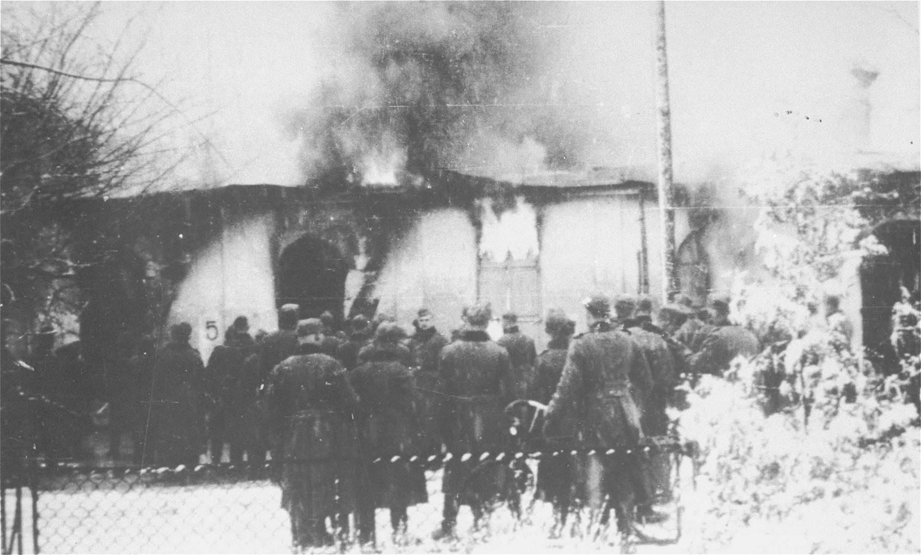 A unit of German soldiers views the burning of a synagogue in Siedlce.