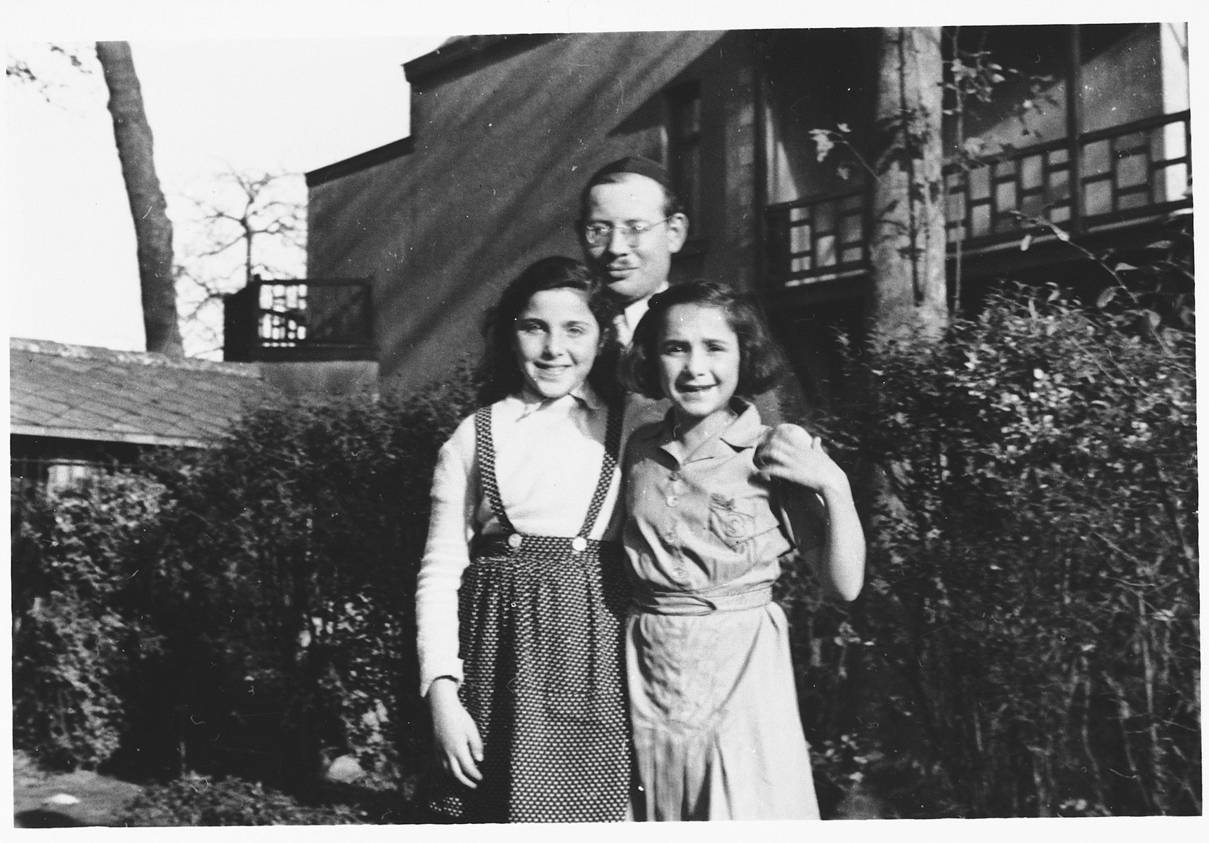 Jonas Tiefenbrunner poses with two girls outside the Mariaburg DP children's home near Antwerp.  Rozette Poler is on the right.