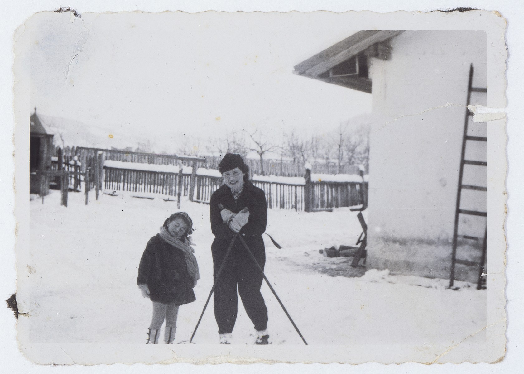 Lida Kleinman and her mother pose in the snow on skis.