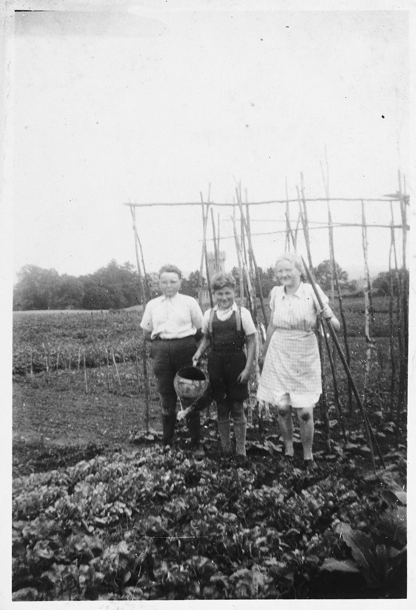 A Jewish child poses with his rescuers in their vegetable garden in Dinant, Belgium.    Pictured is Henri Donner (center) with his foster mother, Ida Alardo, and her son Maurice.