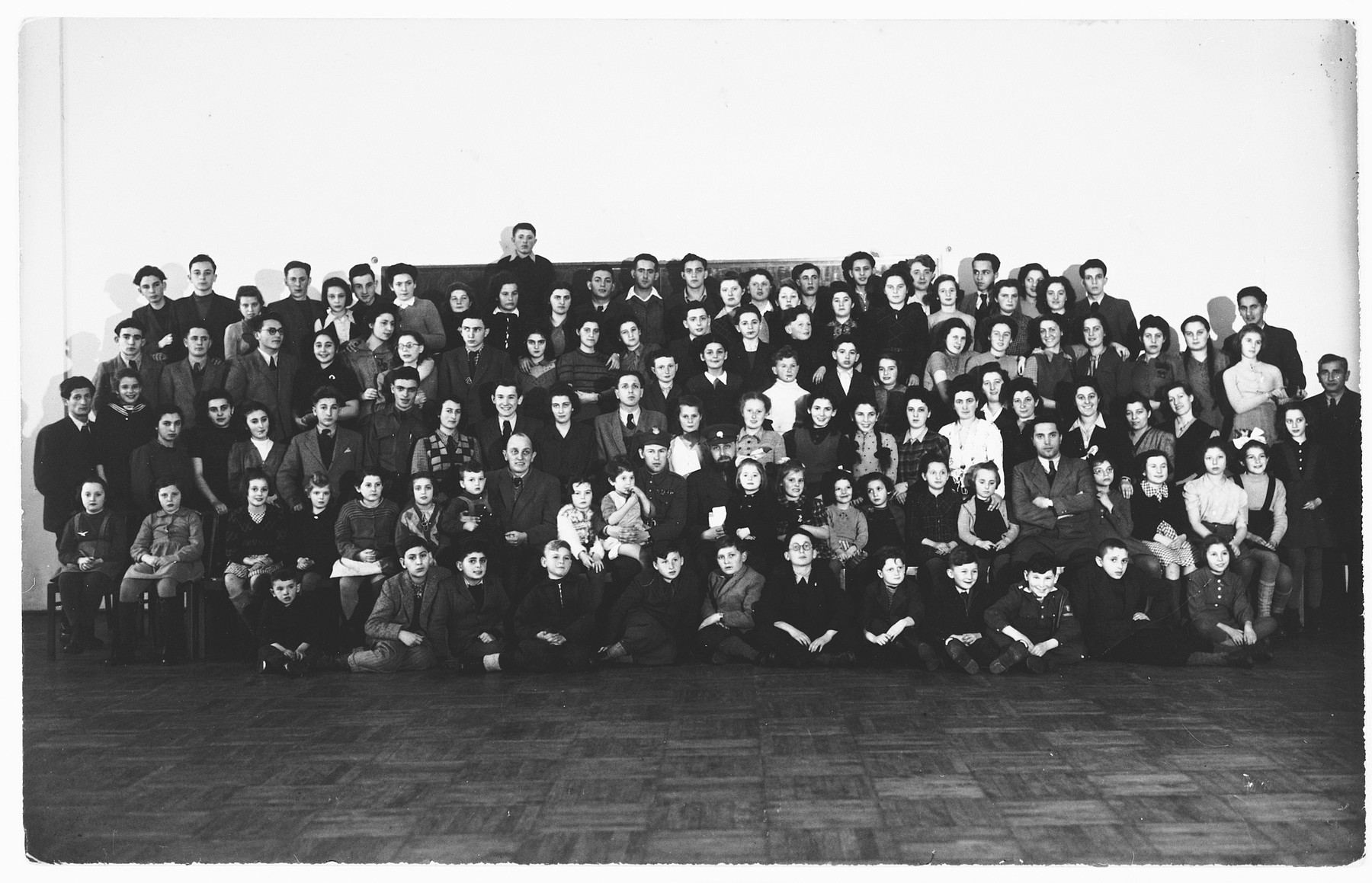 Group portrait of Jewish orphans whom Rabbi Solomon Schoenfeld gathered together to take to England from Poland.  Among those pictured is 14 year old Izio Degenszajn,  standing in the back row extreme left.  He is a survivor of the Warsaw Ghetto. Also pictured are Bianka Rozenman and her cousin Gabriel Zakrzewski.