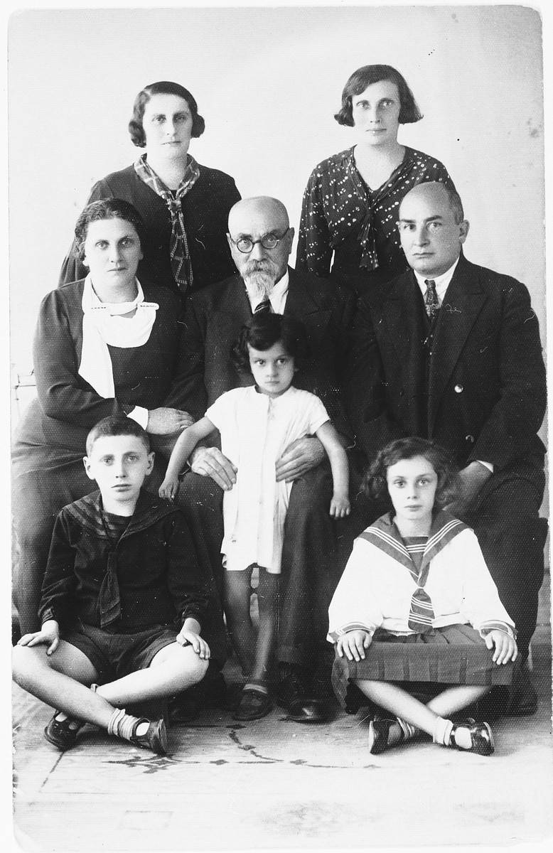 Portrait of the Chasan family taken on occasion of the visit of one of the daughters, Miriam Lipert,  from America.  Pictured sitting are Rochke's son, Kaddish Klausner, and Liza's daughters, Dusya and Sonia.  Middle: Miriam (Mema) Chasan Lipert, her father, Chaim Arye, and Liza's husband, Arye.  Standing are Rochke Klausner and Liza.
