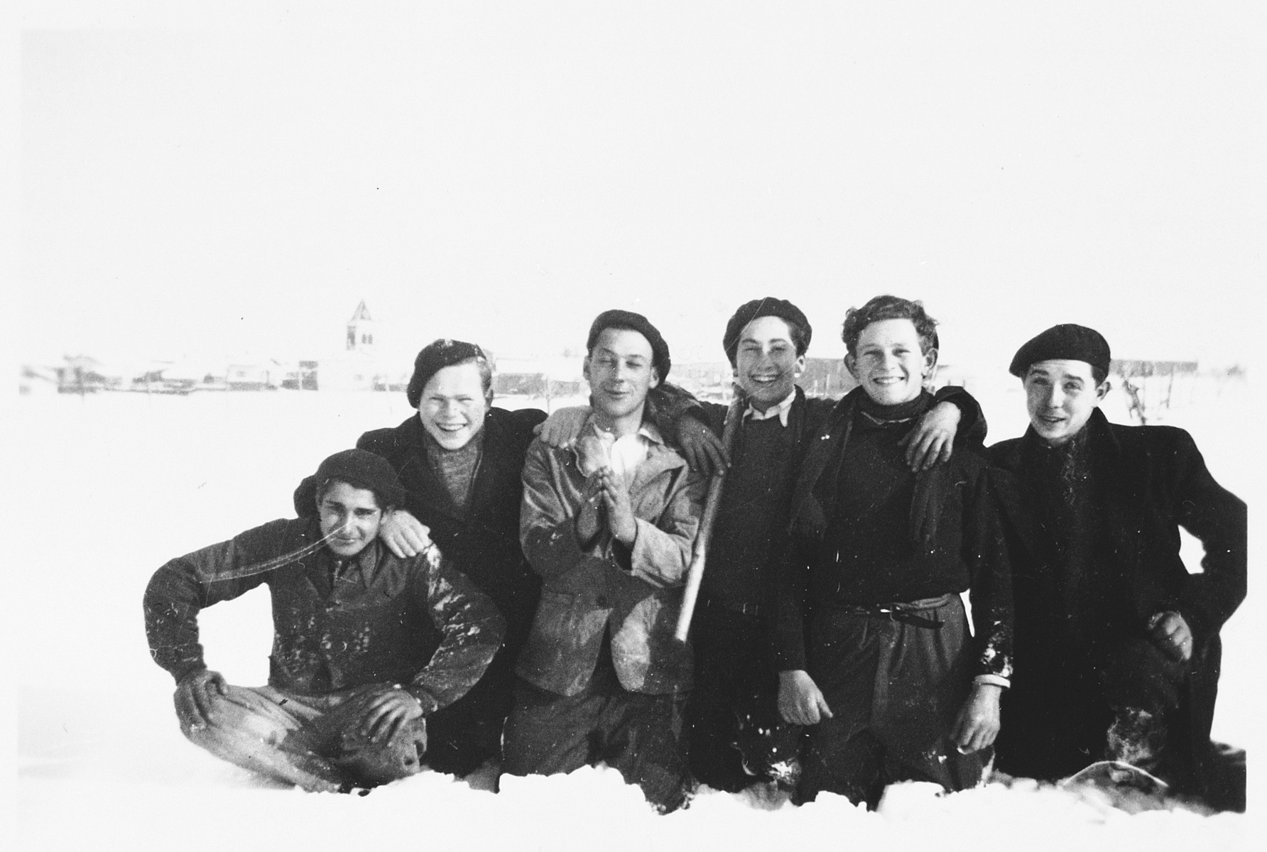 A group of Jewish youth who are living in hiding in the village of Treves, pose in the snow.  Among those pictured are Herbert Karliner (second from the left) and Julien Bluchstein (far right).