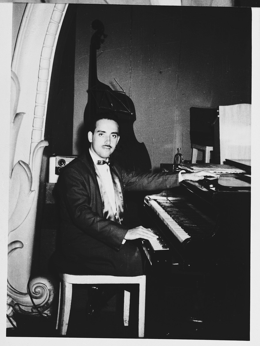 George Taubner, Hungarian Jewish musician, sits by his piano after immigrating to Palestine.