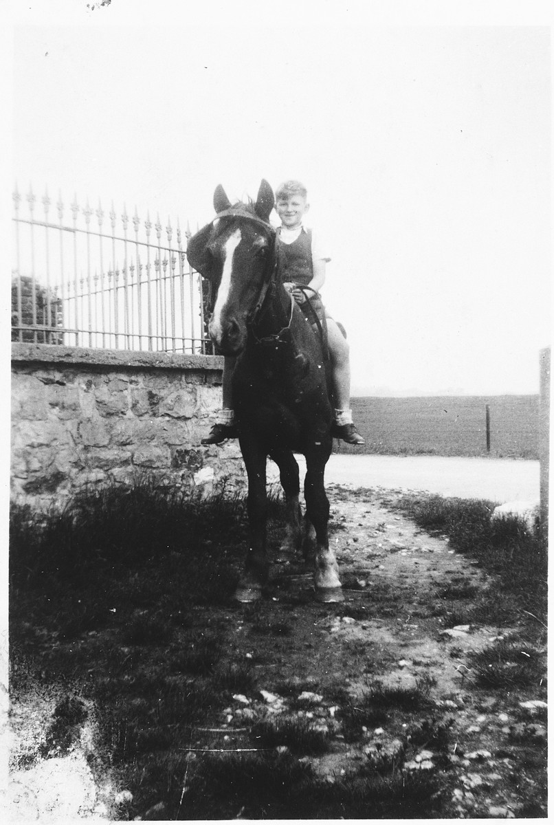 A Jewish child rides a horse on the farm where he was hiding in Dinant, Belgium.  Pictured is Henri Donner.